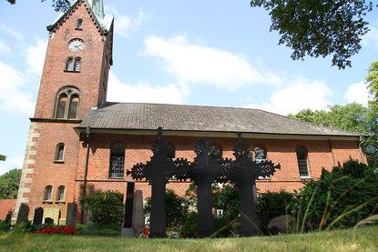 Drei Metallkreuze vor der St.-Nikolai-Kirche in Hohenhorn